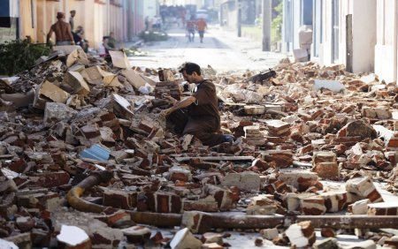 A man salvages bricks from rubble on a street after hurricane Sandy in Santiago de Cuba