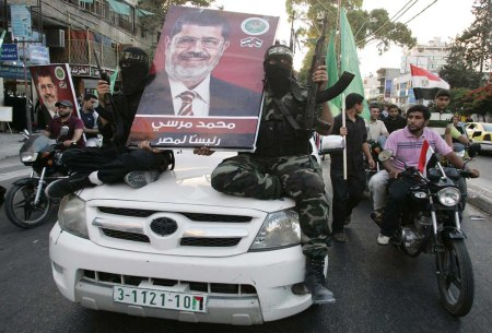 Hamas militants hold a poster depicting Morsy of the Muslim Brotherhood as they celebrate in Gaza City after he was declared Egypt's president