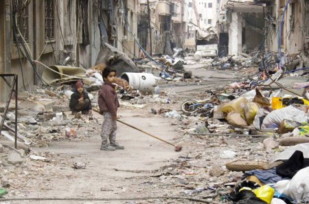 Image: A child clears damage and debris in the besieged area of Homs